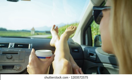 CLOSE UP: Young Caucasian woman resting her feet on the dashboard holds a cup of takeaway coffee during a scenic summer road trip through the countryside. Happy blonde girl enjoying a cup of coffee.
