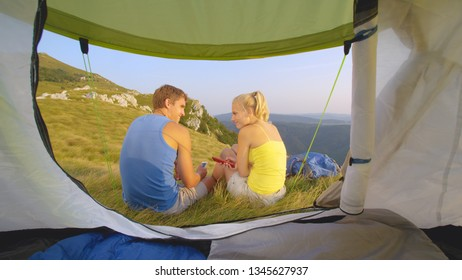 CLOSE UP: Young couple with slouched shoulders sitting in front of their tent and texting their friends. Asocial young man and woman on vacation in the scenic mountains fiddling with their smartphones