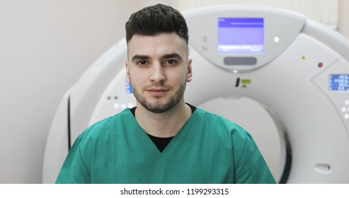 Close up. A young Doctor looking at the camera on a background of a new magnetic resonance imaging. CT and MR scan, scanner, medical examination, Tomograph.