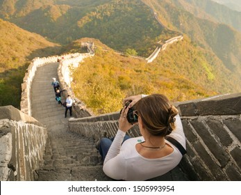 CLOSE UP: Young female photographer takes pictures of the Great Wall and landscape while sitting on step of a steep stairwell. Woman taking photos of the breathtaking landscape and Great Wall of China