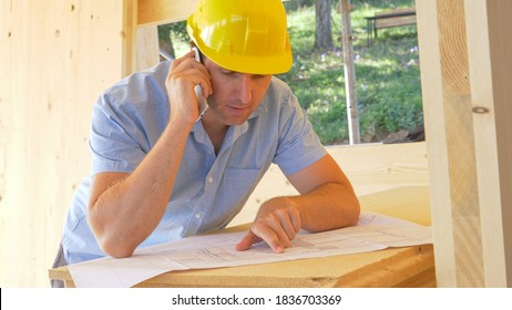 CLOSE UP: Young male construction site manager discusses floor plans over the phone. Caucasian carpenter overseeing the building of a wooden house talks on his smartphone about the final blueprints.