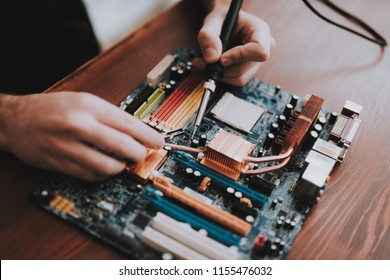 Close up. Young Man Repairing Motherboard from PC. Repair Shop. Worker with Tools. Computer Hardware. Magnifying Glass. Soldering Iron. Digital Device. Laptop on Desk. Electronic Devices Concept.