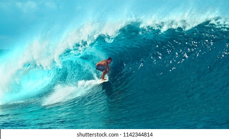 CLOSE UP: Young pro surfer surfs a big barrel wave in popular surf spot in breathtaking Tahiti. Awesome view of a extreme surfboarder riding epic blue waves in the hot summer sun of French Polynesia.