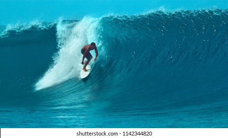CLOSE UP: Young sportsman riding a big crystal clear tube wave while on awesome summer vacation in Tahiti. Extreme athlete surfing a spectacular barrel wave in sunny French Polynesia. Fun water sport.