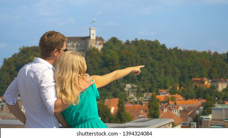 CLOSE UP: Young woman observing the scenic town with her boyfriend from a rooftop. Unrecognizable traveler couple observe the Ljubljana castle and cityscape from a scenic rooftop in the city centre