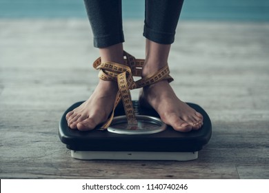 Close up. Young Woman Standing on Weigher on Floor. Diet Concept. Weight Loss Problem. Starving Young Woman. Tailors Centimeter. Hungry Woman. Healthy Lifestyle Concept. Wooden Floor.