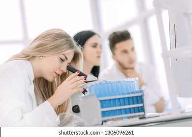close up.a modern female scientist looks into a microscope in a laboratory