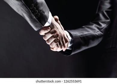 close up.business handshake isolated on black background.photo w