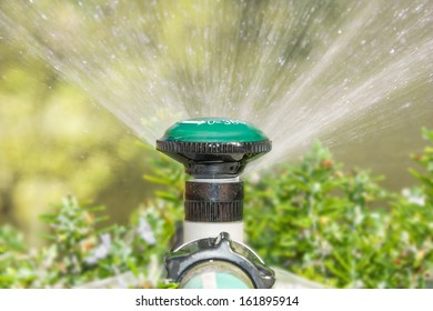 Close up,garden sprinkler head,water spray.Plastic sprayer head mounted on pipe, connected to hose.Can be rotated to 360 degrees for full spray.White arrow,numbers painted on head.Low angle view.