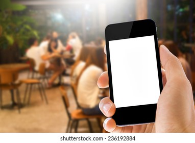 Close uphand holding phone with blank screen on coffee cafe background