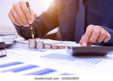 Close up,Hand putting money coins stack in saving money and growing business concept.