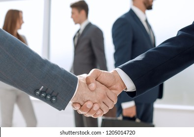 close up.handshake business partners in the background of the of