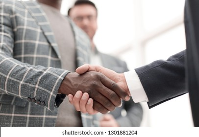 close up.handshake entrepreneurs on the background of the office.