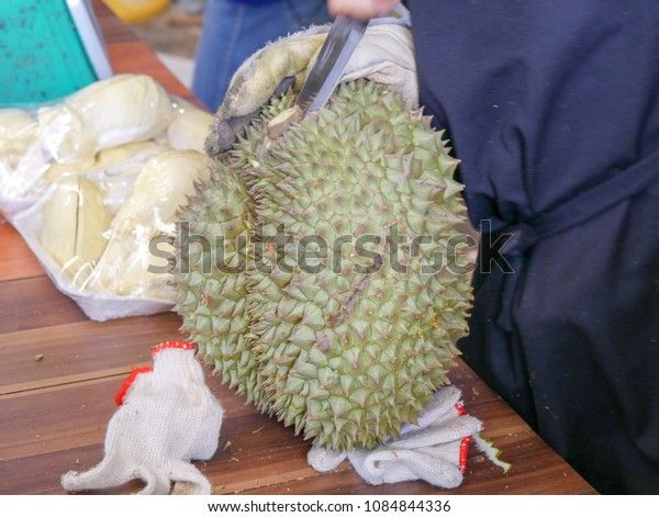 Close up,Man peeling fresh durian or king of fruit on old wood table