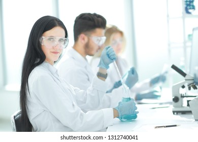 close up.modern woman sitting with colleagues at the laboratory table.