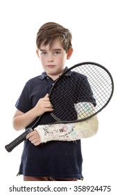 Close up upper body shot of a cute young boy who has broken his left arm and is unhappy because he can't play tennis