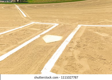 Close ups of dirt baseball diamond from a public park with newly painted baselines and batters box.