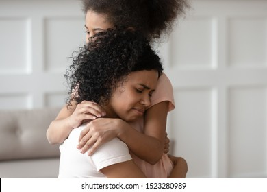Close up upset loving affectionate african american young woman embracing little kid daughter, give support, helping with problems or bullying, comforting, expressing love, feeling sorry, apologizing