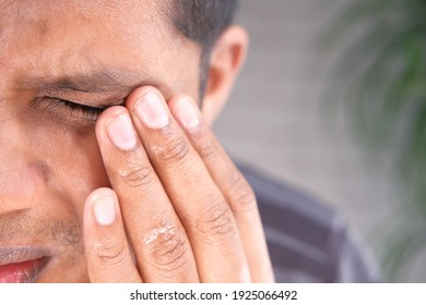Close up of upset man suffering from strong eye pain