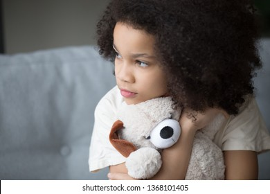 Close up upset stray biracial kid girl sitting on sofa cuddle stuffed toy dog looks aside feel lonely unhappy. Preschool age orphan, bullying discrimination, depression, psychological trauma concept