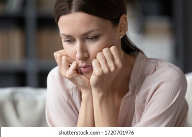 Close up upset young woman thinking about problems, sitting alone, unhappy hopeless beautiful female holding face in hands, feeling depressed, break up with boyfriend, relationship troubles
