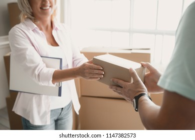 Close up.Smiling Blonde Woman Takes Small Box from Hand to Hand. Boxes in the Background. Moving House Concept. Courier Work. Young Man in Room. New Apartment Concepts. Woman with Box.