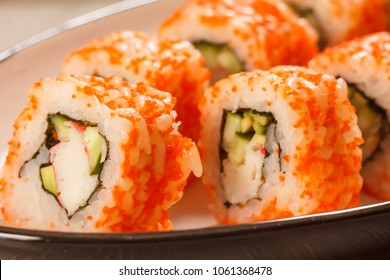 Close up Uramaki California. Sushi rolls with nori, rice, pieces of avocado, cucumber, crab sticks decorated with flying fish roe on ceramic plate. Japanese cuisine. Shallow depth of field
