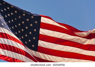 Close up of the USA flag waving in the wind against blue skies