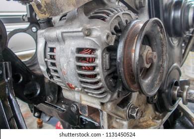 Close up of used alternator over a car engine.