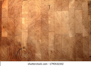 An close up of a used butcher's block with lots of knife marks and scratches