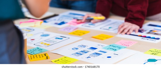 Close up ux developer and ui designer brainstorming about mobile app interface wireframe design on table with customer brief and color code at modern office.Creative digital development agency.panning - Shutterstock ID 1740168170