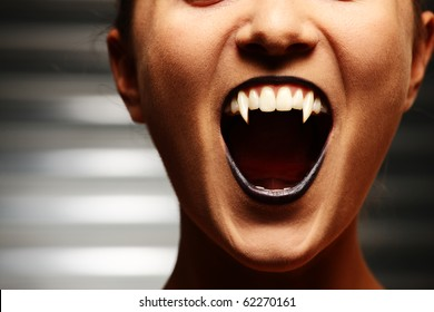Close up of a vampire woman's mouth over dark background