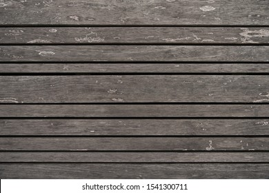 Close up of varied horizontal wooden strips on a bench with slight weathering