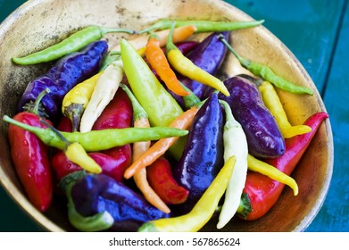 Close up of various colorful fresh chili peppers, paprika on rustic wooden teal table, in golden bowl, rain drops, reflections, space for text, top shot, selective focus
