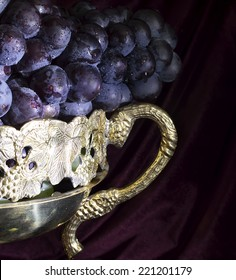 Close up of vase with bunch of grapes on velvet background