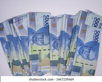 Close up vast top view of Flat lay stack packs of bundle Banknotes series uang idr 50000 rupiah fifty thousands indonesia money isolated on white background. New fresh from Bank Indonesian currency