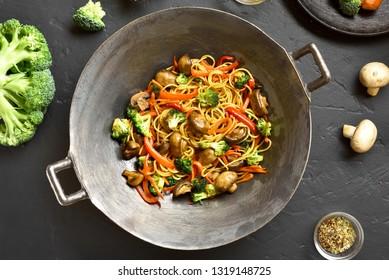 Close up of vegan vegetarian stir-fry noodles with vegetables in wok pan on black stone background.  Stir-fry noodles with vegetables in asian style. Top view, flat lay