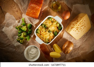 Close up of vegetable casserole with cheese salmo, chicken on kitchen table. Flatlay of salmo pudding (pie) on wooden background. Rustic homemade casserole. Healthy vegetarian cuisine.