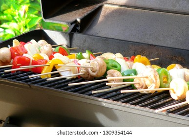 Close up of vegetables on bamboo skewers on a outdoor grill including mushroom, peppers, and onions
