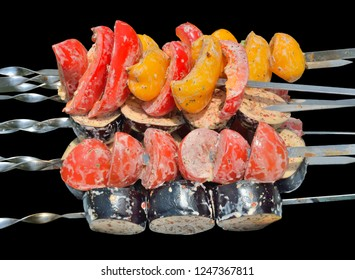 A close up of the vegetables on skewers. Isolated on black.
