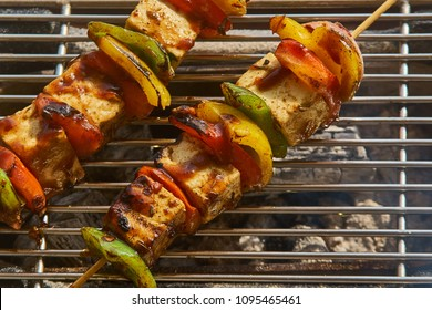 A close up of a vegetables on a stick on a grill.