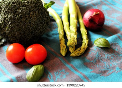 Close up of vegetables in spring: Green aspargus, broccoli, tomatoes, onion and basil leaves decorated on a tea towel.