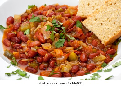 Close up of vegetarian chili with beans, and cornbread in a white bowl.