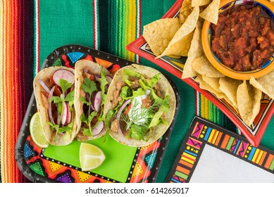 Close up of vegetarian corn tacos  with refried beans and vegetables on the Fiesta table.