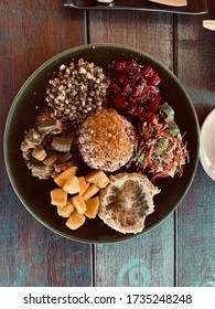 Close up of vegetarian food plate with okra, quinoa, slam humus, pumpkin and beat. Served on a green plate on a wooden table top view. Vikasa Life Cafe in Ko Samui