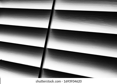 Close up of venetian blinds with light seeping through outside rendered in black ansd white in abstract form
