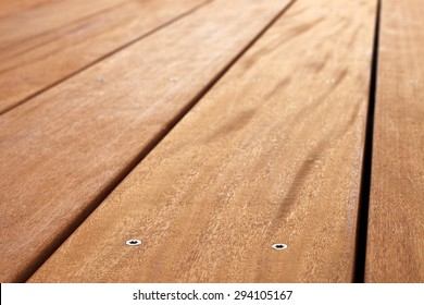 Close up of a veranda floor, made from garapa wood. With shallow depth of field.