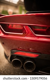 Close up vertical image of the LED tail lights and exhaust pipes of a new sport super car.