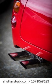 Close up vertical image of the red tail light and exhaust pipes of a white classical vintage car.