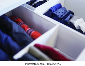 Close up of vertical storage of men's undergarments in closet drawer - tidying up and organizing your clothes and home - minimalism decluttering concept